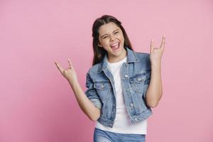 Mischievous, cheerful teenage girl showing rock gesture with fingers photo