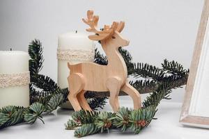 Three Christmas candles, branch of pine and wooden deer photo