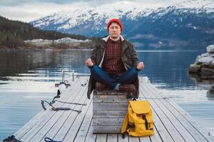 Traveler man in a meditative pose on a pier on background of mountain photo