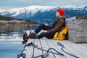 Traveler man sitting on wooden pier on background of mountain and lake photo