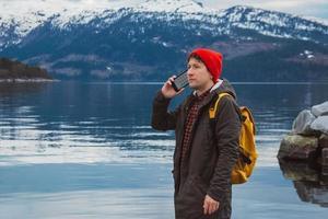 Hombre viajero hablando por teléfono móvil frente a la montaña foto