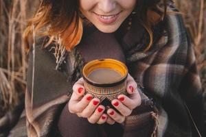 Beautiful girl covered with a plaid holding a hot cup photo