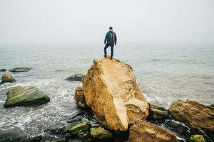 Traveler man with a backpack stands on a rock against a beautiful sea photo