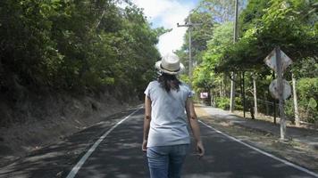 femme portant un chapeau de paille marchant sur la route dans le parc video