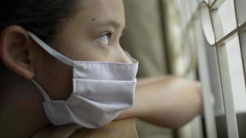 Girl Wearing Protective Mask Looking out Of Window During Quarantine video