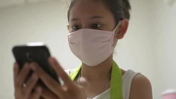 Girl Wears Face Mask While Using Smartphone for Online Communication at Home video