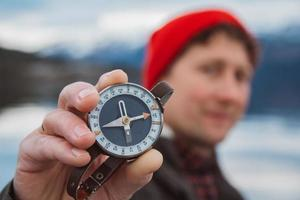 Traveler man holds an old compass against photo