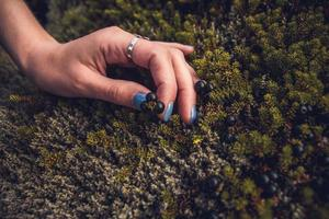 Woman touching the stone moss in nature and exchanging emotion energy photo