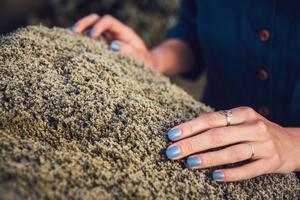 Mujer tocando el musgo de piedra en la naturaleza e intercambiando energía emocional. foto