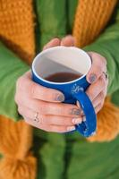 Woman's hand holding a cup of hot coffee photo