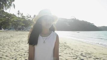 une fille heureuse porte un chapeau de paille marchant sur la plage sous la lumière du soleil d'été video