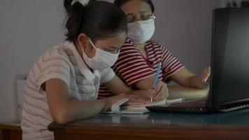 Girl and Her Mom Wear Face Mask While Watching Lesson Online from Laptop video