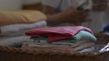 Mujer doblando la ropa y la pone en una canasta de madera en la cama. video