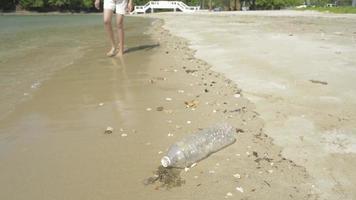 jovem coletando resíduos de garrafas plásticas na praia video