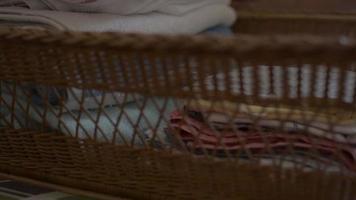 La madre dobla la ropa y la pone en una canasta de madera. video