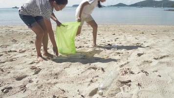 mãe e filha recolhendo lixo na praia em um saco plástico video