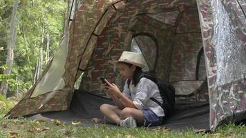 fille avec sac à dos assise et utilisant un téléphone portable devant la tente video