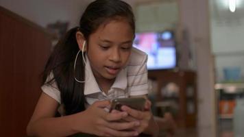 Adolescente femenina viendo videos musicales desde un teléfono inteligente con auriculares