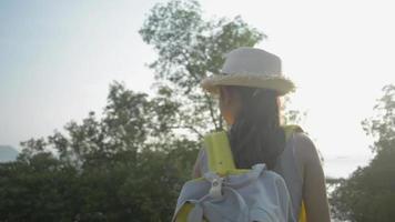 fille asiatique avec sac à dos bénéficie de beaux paysages pendant le coucher du soleil video