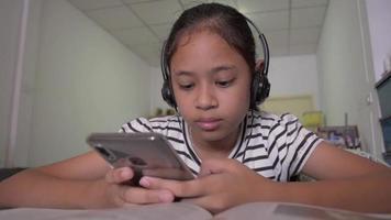 linda garota assistindo vídeo online de telefone inteligente com fone de ouvido em casa video