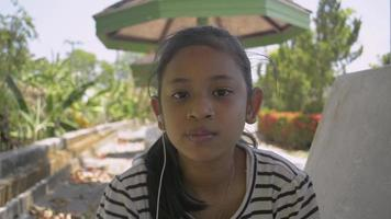 Happy Girl Wearing Earphones and Eating Ice Cream in Public Park video