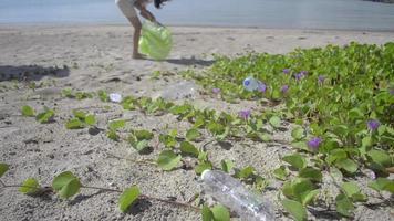 jovem coletando lixo plástico na praia em um saco plástico video