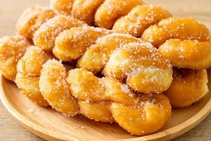 Sugar doughnut in a spiral shape on wooden plate photo