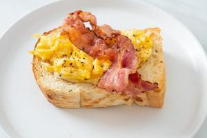 Bread toast with scramble egg and bacon on white plate photo