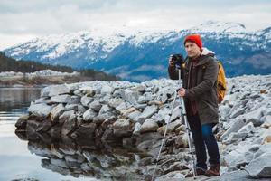 Travel photographer man taking nature video of mountain landscape photo