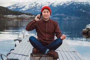 Hombre viajero hablando por teléfono móvil en el muelle de madera foto