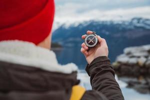 Traveler man holds an old compass against of the mountain and a lake photo