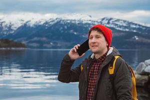 Retrato hombre viajero hablando por teléfono móvil contra de la montaña foto