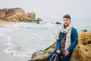 Hombre con una mochila de pie cerca de una roca frente a un hermoso mar foto