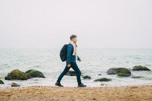 Man with a backpack standing near a rock against a beautiful sea photo