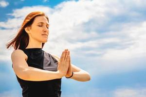Portrait  woman relaxing yoga position against sky background photo