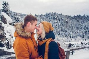 Loving couple cuddling outdoors in a snow landscape photo