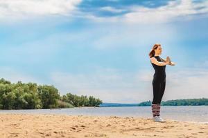 Woman doing yoga on a sandy beach photo