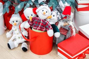 Funny toy snowmen and presents under decorated fir tree photo