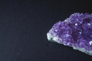 Cristal de amatista púrpura sobre fondo negro foto