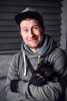 Man is a photographer with camera. Funny Face. Dark gray background photo