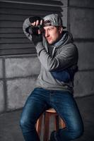 Man is a photographer with camera on a chair in a dark room photo