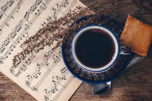 Hot drink with musical notes on a wooden table surface photo