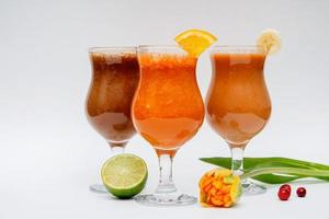 Fruit juices in glasses on a white background photo