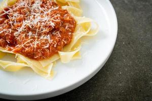 Pork bolognese fettuccine pasta with parmesan cheese - Italian food style photo