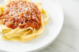 Pasta fettuccine a la boloñesa de cerdo con queso parmesano - estilo de comida italiana foto