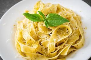 Pesto fettuccine pasta with parmesan cheese on top - Italian food style photo