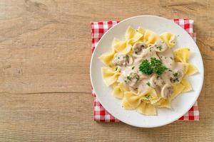Pasta farfalle con salsa de crema blanca de champiñones - estilo de comida italiana foto