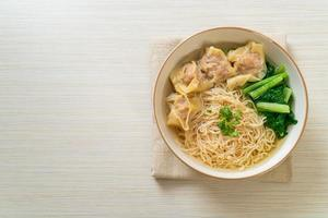 Fideos de huevo con sopa de wonton de cerdo o sopa de albóndigas de cerdo y verduras - estilo de comida asiática foto