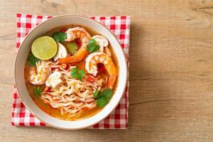 Instant noodles ramen in spicy soup with shrimps - Tom Yum Kung - Asian food style photo
