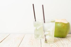 Coconut water or coconut juice in glass with ice cube photo